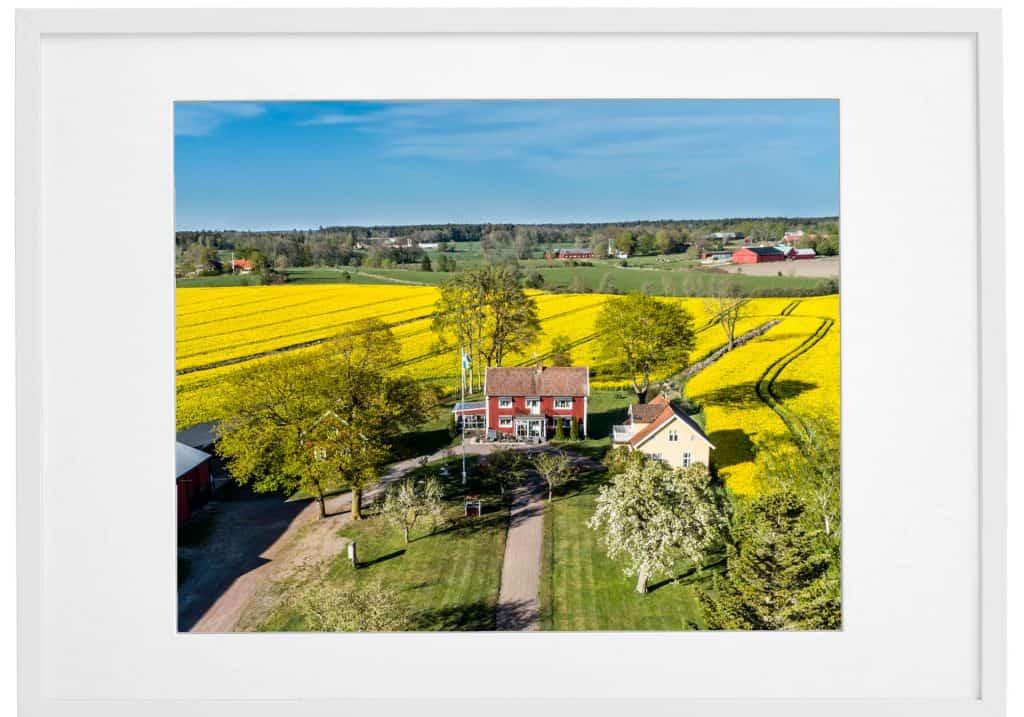 Hus-foto erbjuder inramade dekorativa flygfotografier för villor, hus och fastigheter. Här visas ett exempel i vit ram.